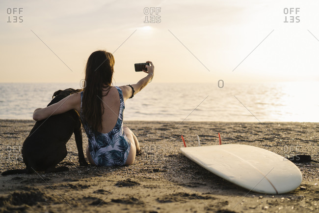 Back view of young surfer sitting on the beach with her dog taking selfie with smartphone- Almeria- Spain