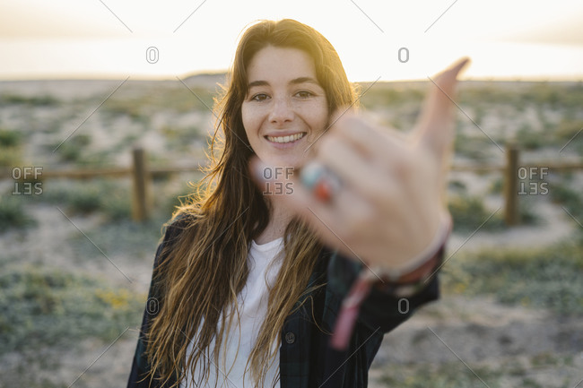 Portrait of smiling young woman showing shaka sign