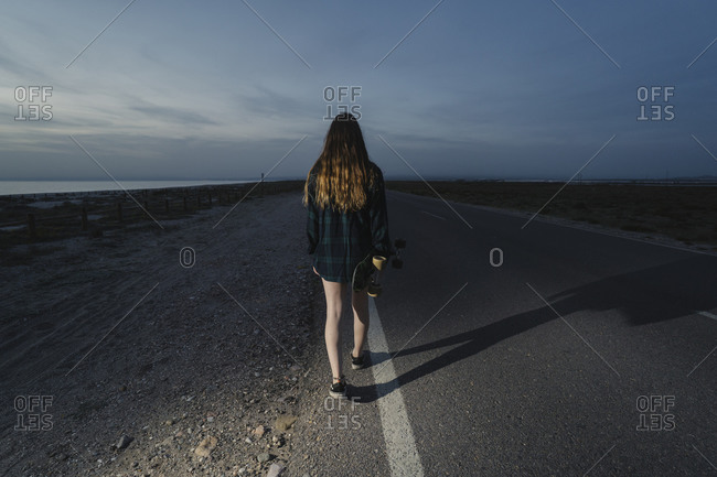 Back view of young woman with skateboard walking along asphalt road- Almeria- Spain