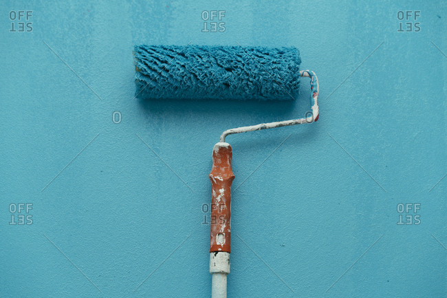 Studio shot of blue paint roller against blue background
