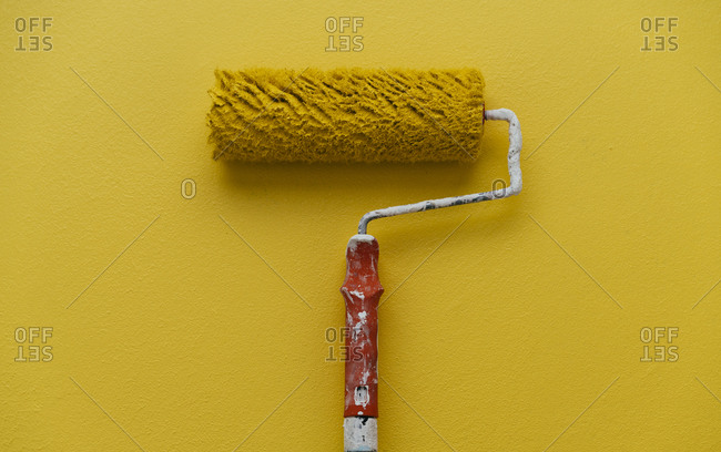 Studio shot of yellow paint roller against yellow background