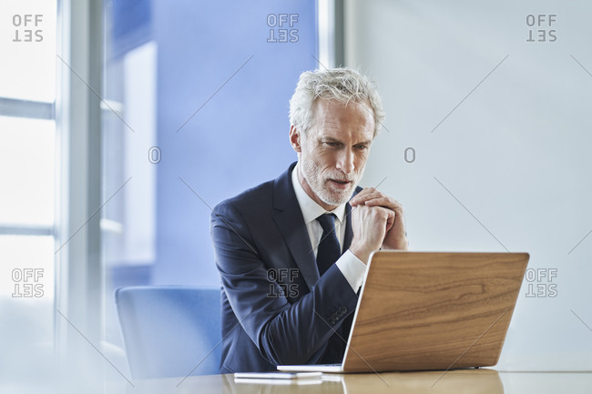 Focused businessman using laptop at desk in office