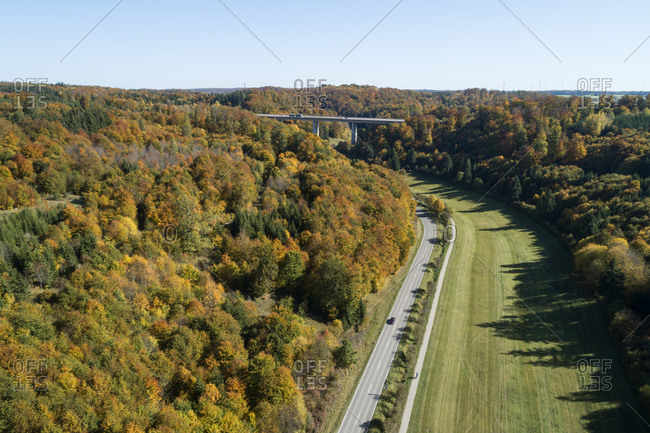 Germany- Baden-Wurttemberg- Heidenheim an der Brenz- Drone view of highway stretching along edge of autumn forest