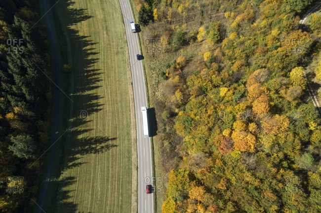 Germany- Baden-Wurttemberg- Heidenheim an der Brenz- Drone view of traffic on highway stretching along edge of autumn forest