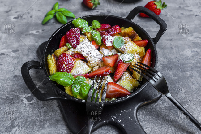Pan of Kaiserschmarrn with strawberries- powdered sugar and basil