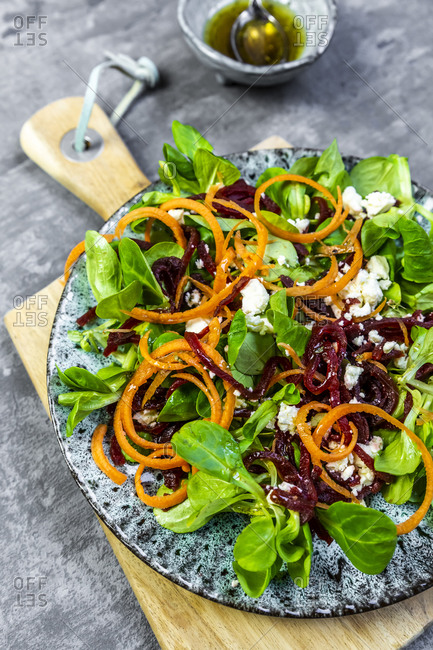 Plate of vegetarian corn salad with feta cheese- carrot strips and beetroot strips