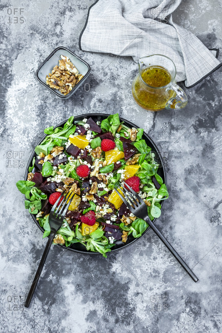 Plate of mixed salad with feta cheese- beetroot- walnuts- corn salad- raspberries- oranges and pine nuts