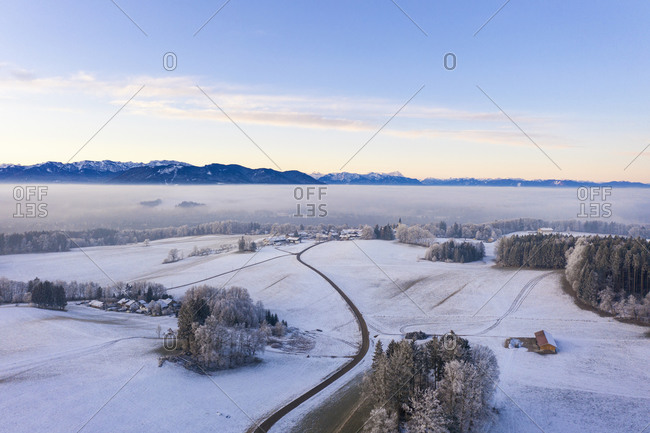 Germany- Bavaria- Hechenberg- Drone view of snow-covered countryside village at foggy dawn