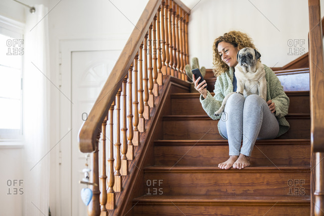 Woman sitting on stairs- using smartphone with pug on her lap