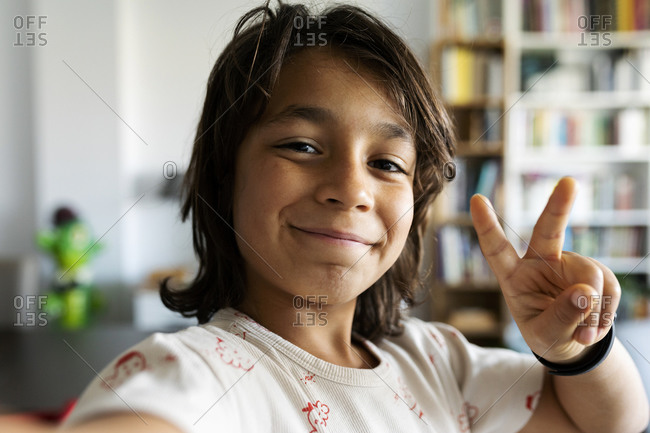 Portrait of smiling boy at home showing victory sign