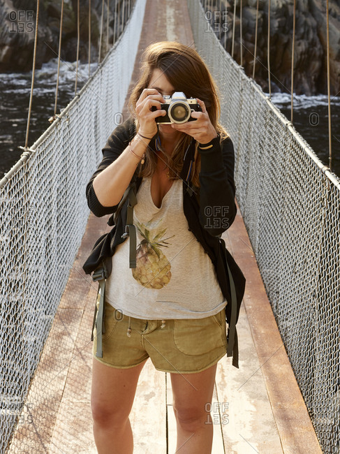 Woman on a suspension bridge taking a picture with her camera- Tsitsikamma National Park- South Africa