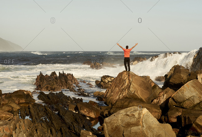 Man on the rocks in front of the ocean. Tsitsikamma National Park- South Africa