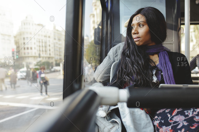 African-American woman looking out the window of the bus