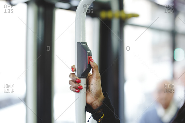 A woman's hand pressing the bus stop button