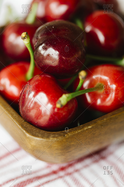 Wood bowl of fresh cherries on a red striped napkin