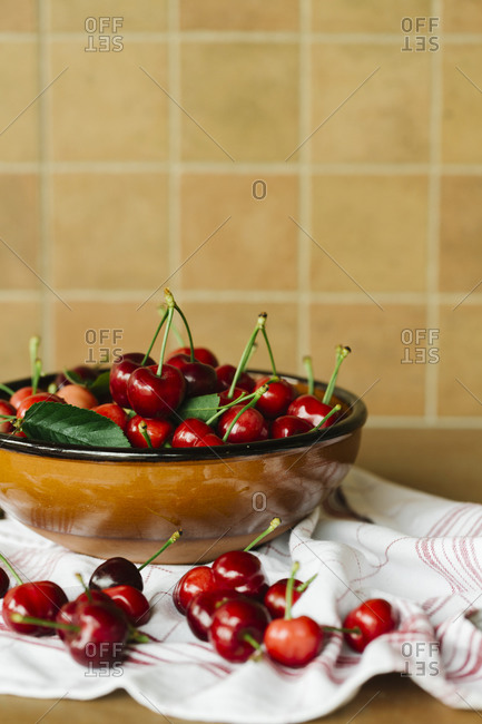 Fresh cherries in a ceramic bowl on a red striped napkin