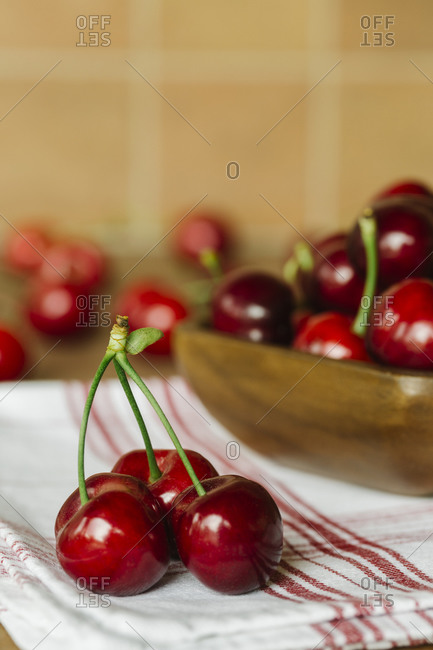 Fresh cherries in a wooden bowl on a red striped napkin