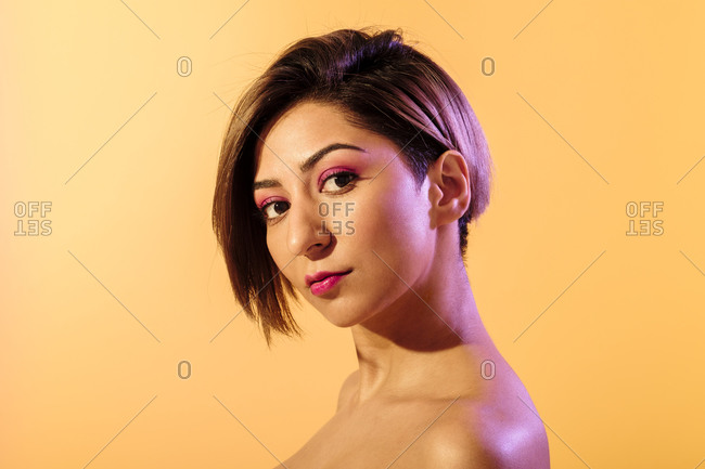 Soft skin beautiful woman with short hair on a yellow background illuminated with purple light
