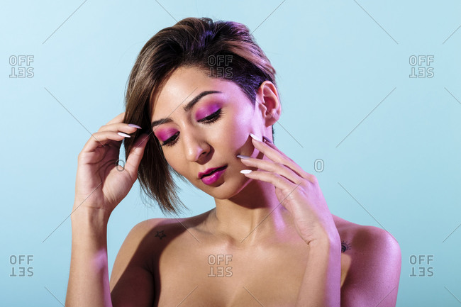 Soft skin beautiful woman with short hair on a blue background illuminated with purple light