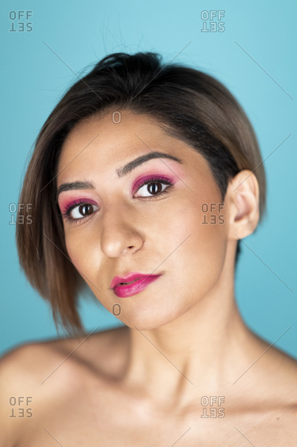 Looking at camera portrait of a beautiful woman with soft skin on a blue background