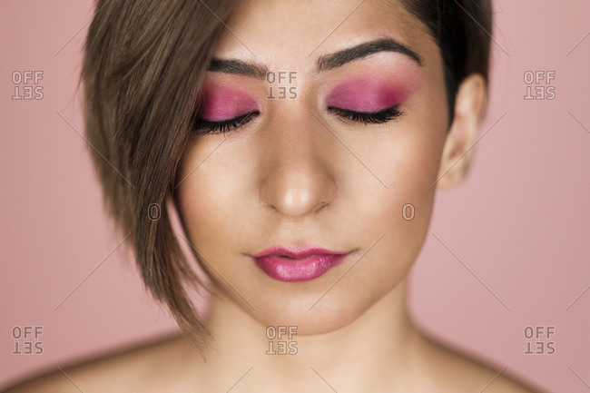 Closed eyes portrait of a beautiful woman with soft skin on a pink background