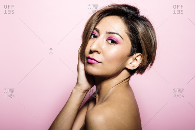 Looking at camera portrait of a beautiful woman with soft skin on a pink background