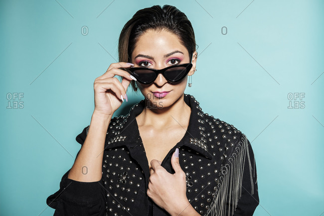 Beautiful woman portrait wearing a leather jacket and jeans with sunglasses on a blue background