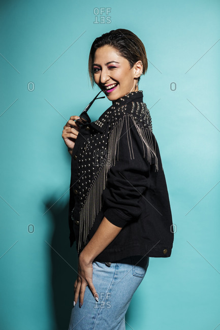 Beautiful smiling woman portrait wearing a leather jacket and jeans with sunglasses on a blue background