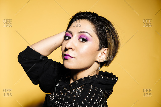 Beautiful woman portrait wearing a leather jacket and jeans with sunglasses on a yellow background