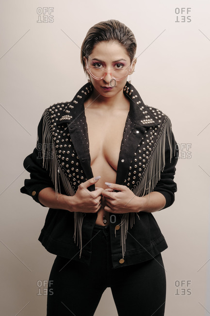 Beautiful woman portrait wearing a leather jacket and black jeans with glasses