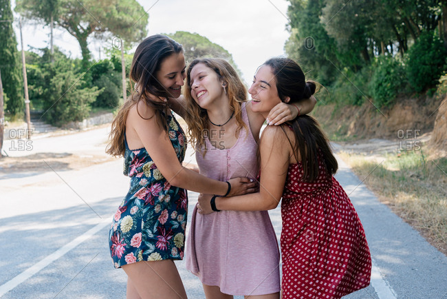 Three happy young teenagers hugging and smiling outdoors on a mountain road