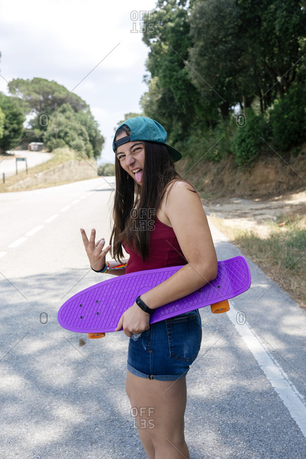 Girl holding a skateboard while waving her hands and sticking out her tongue