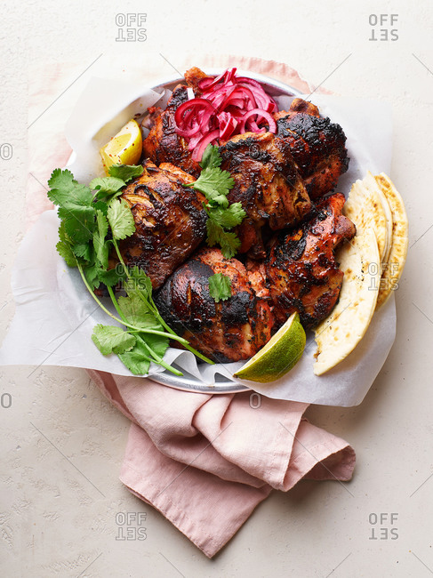 Overhead image of tandoori chicken thighs marinated in tikka sauce, grilled and served with mint chutney, lime and cilantro. Traditional indian cuisine starter.