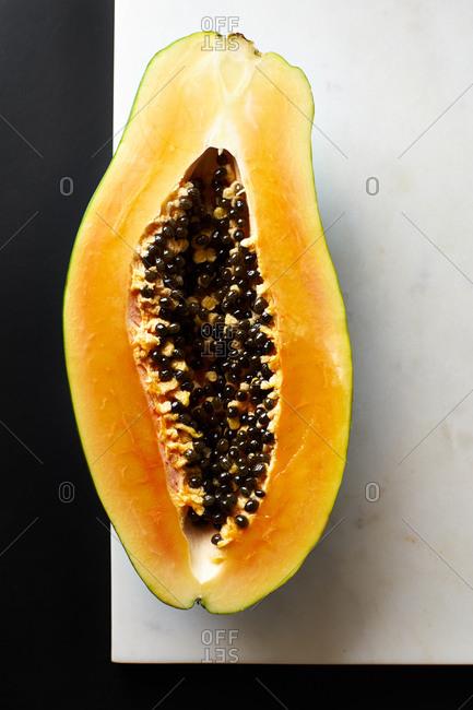 Sliced papaya on marble cutting board on black background