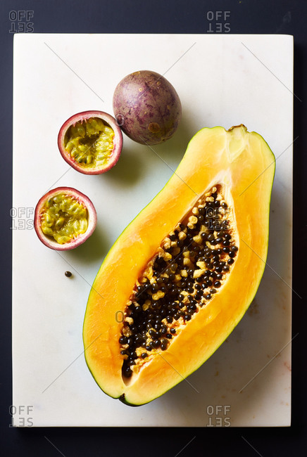 Sliced papaya and passion fruit on marble cutting board on black background
