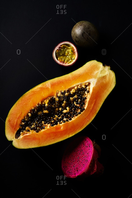 Still life with sliced papaya, pitaya and passion fruit on black background
