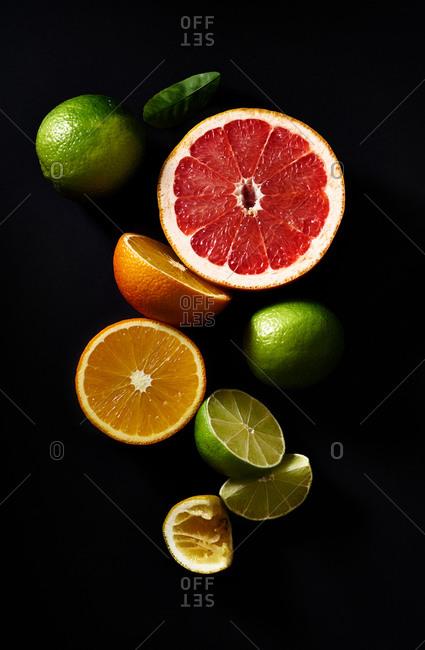 Sliced citrus fruits on black background: grapefruit, lime, orange, lemon