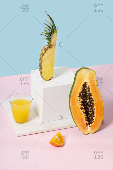 Still life with pineapple slice, white cube, papaya half and a glass of orange juice on colorful background