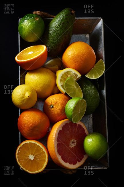 Sliced citrus fruits in a tray on black background: grapefruit, lime, orange, lemon