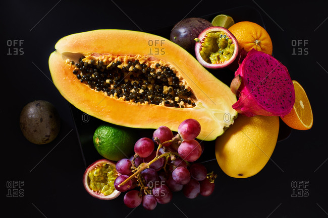 Still life with sliced papaya, grapes, pitaya and tropical fruits on black background