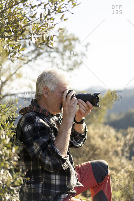 Senior man photographing in nature