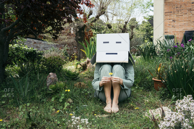 Young woman with cardboard box on her head sitting barefoot in garden