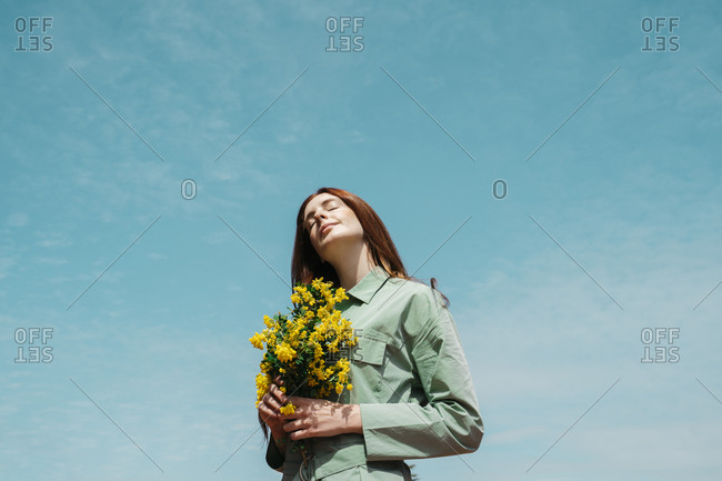 Portrait of redheaded young woman with eyes closed standing against sky holding bunch of yellows flowers