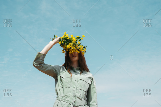 Redheaded young woman against sky covering eyes with bunch of yellow flowers