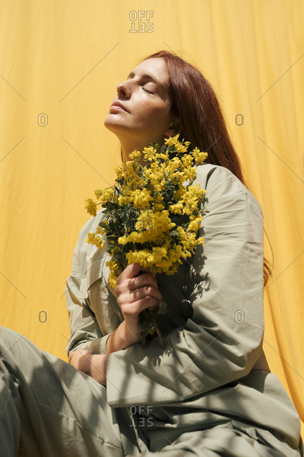 Portrait of redheaded woman with eyes closed holding bunch of yellow flowers against yellow background