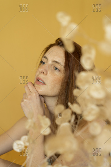 Portrait of pensive redheaded woman against yellow background