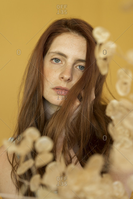 Portrait of redheaded woman against yellow background