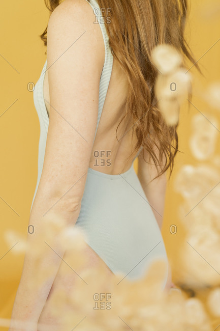 Crop view of Portrait of redheaded woman against yellow background