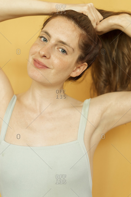 Portrait of smiling redheaded woman tying hair against yellow background