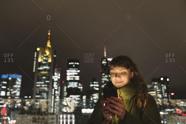 Germany- Hesse- Frankfurt- Portrait of adult woman using smart phone against city skyline at night